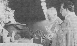 Archbishop Lefebvre reads from a missal at the altar, beside Fr. Natterer